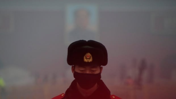 A paramilitary police officer wearing a mask stands guard in front of a portrait of the late Chairman Mao Zedong during smog at Tiananmen Square after a red alert was issued for heavy air pollution in Beijing, China, December 20, 2016.