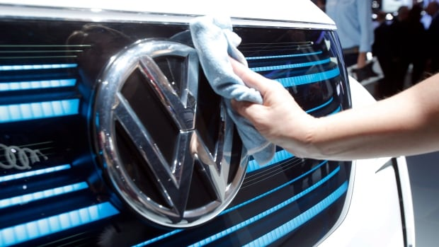 A worker shines the grill of a new Volkswagen electric car during a press conference at the Paris Motor Show in Paris in Sept. 2016. The company was ordered to pay at $2.8 billion US criminal penalty on Friday stemming from an emissions scandal.
