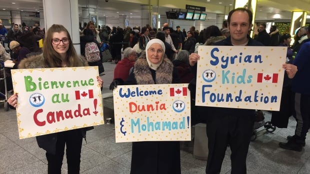 Syrian Kids Foundation executive director Faisal Alazem, left, and volunteers hold signs at Montreal's Trudeau Airport as they wait for two Syrian refugees about to begin their studies at Concordia University.