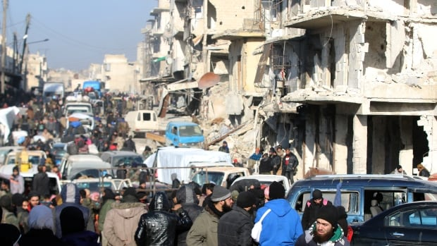 Rebel fighters and civilians wait near damaged buildings to be evacuated from a rebel-held sector of eastern Aleppo on Dec. 18.