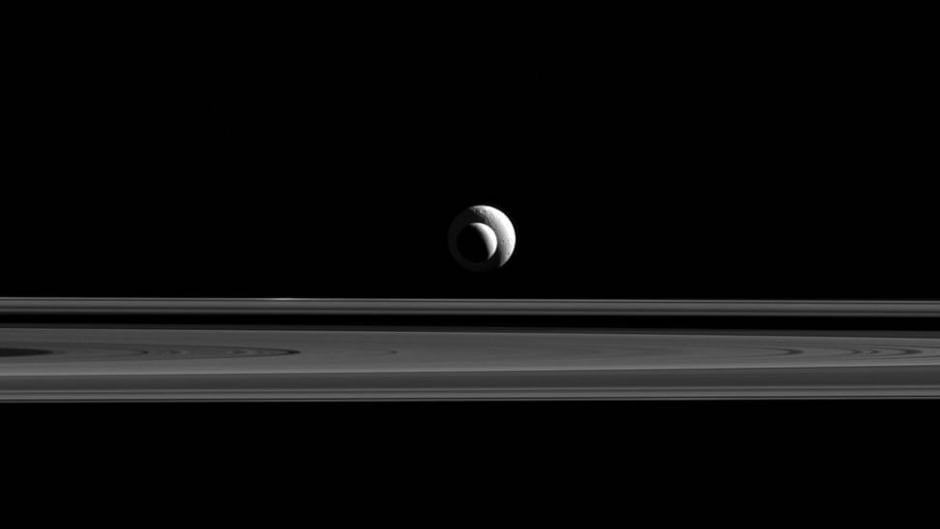 Two of Saturn's moons, Enceladus (504 kilometers across) and Tethys (1,062 kilometers across). The clean ice of Enceladus may make it a good place to search for alien life.