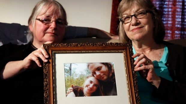 In this June 2014 file photo, mothers Linda Boyle, left, and Lyn Coleman hold a photo of their married children, Joshua Boyle and Caitlan Coleman, who were kidnapped by the Taliban in late 2012.