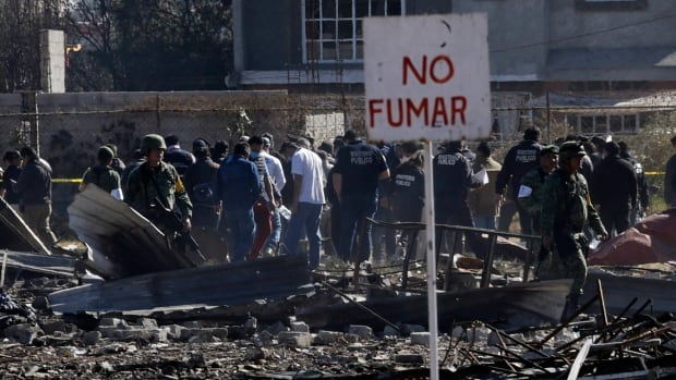 A 'no smoking' sign stands above the scorched rubble of the open-air San Pablito fireworks market that exploded in Tultepec on the outskirts of Mexico City on Tuesday, killing dozens of people and leaving others badly burned.