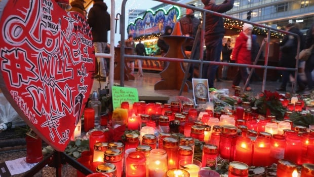 Visitors walk past a makeshift memorial at the reopened Breitscheidplatz Christmas market only a short distance from where a truck plowed into the market, killing 12 people in Berlin.