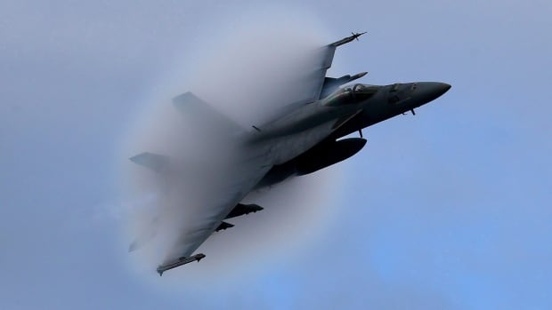 A F-18 Super Hornet creates a vapor cone as it flies at a transonic speed while doing a flyby of the USS Eisenhower off the coast of Virginia in 2015. Canada plans to buy 18 Boeing Super Hornet fighter jets to fill the gap until the government chooses a permanent replacement for the aging CF-18s.