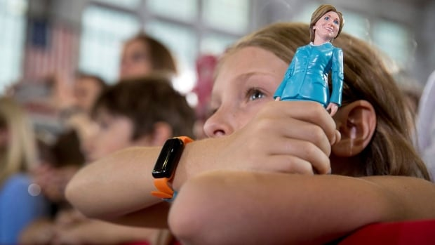 A girl in the audience holds a figurine of Democratic presidential candidate Hillary Clinton as Clinton speaks at a rally in Akron, Ohio, Oct. 3.