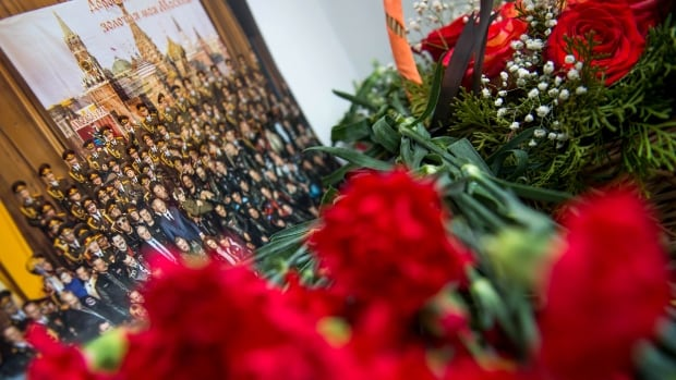 A picture and flowers are seen at the home stage building of the Alexandrov Ensemble (The Red Army Choir), in Moscow on Dec. 25. Members of the choir were among those on board a Russian military plane that crashed early Sunday.