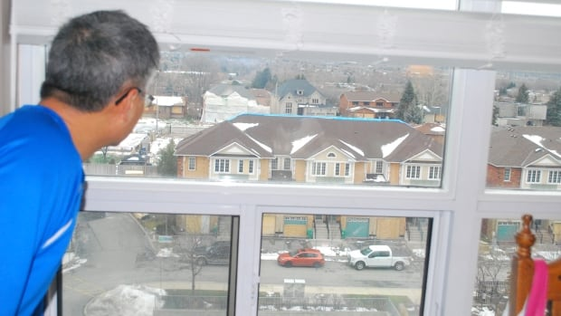 Frank Mo looks down at the repairs on his town home from his rented sixth-floor condo.