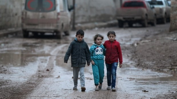 Children walk near a parked ambulance in al-Rai, in Syria's northern Aleppo province, on Wednesday. Turkey and Russia are reportedly close to agreeing on a Syrian ceasefire.
