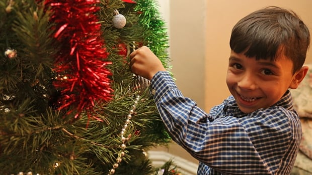 Abdallah Al Rahmo, 6, hangs an ornament on his family's Christmas tree this month. A group from Dundas and west Hamilton sponsored his 14-member family's immigration to Canada. They fled Aleppo because of the bloody Syrian civil war.