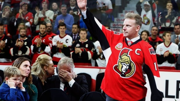 Former Ottawa Senators player Daniel Alfredsson makes his way to the ice as his father Hasse Alfredsson (centre) is comforted by his daughter Cecelia Sable and Alfredsson's wife Birgitta and son Fenix look on. Alfredsson's No. 11 was retired Thursday evening at the Canadian Tire Centre.