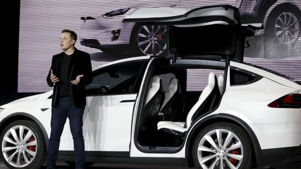 Tesla Motors CEO Elon Musk introduces the falcon-wing door on the Model X electric sports-utility vehicles during a presentation in Fremont, Calif.