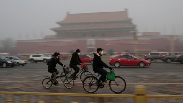 People wearing masks cycle past Tiananmen Gate during the smog after a red alert was issued for heavy air pollution in Beijing.