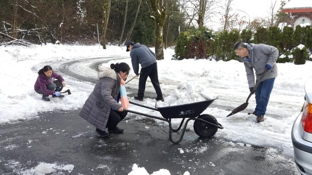 Burnaby's Yan family use an axe, two shovels and wheelbarrow to try and clear the ice and snow from their driveway.