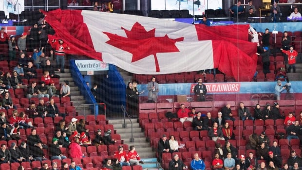 There are many empty seats as fans pass around a giant Canadian flag before the quarter-final IIHF World Junior Championships hockey game between Czech Republic and Canada on Monday in Montreal. Canada won to advance to Wednesday's semifinals.