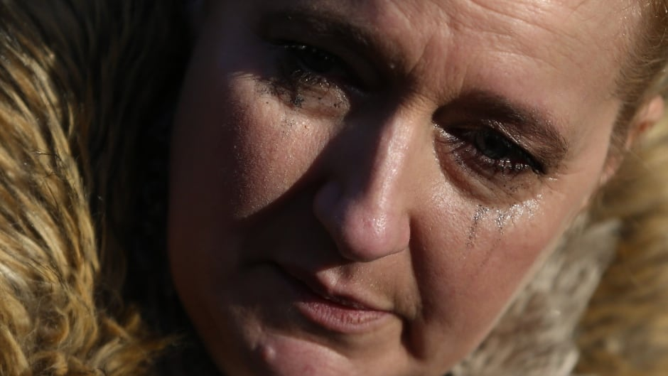 A woman reacts as she views tributes to singer George Michael outside of his home in north London, England.
