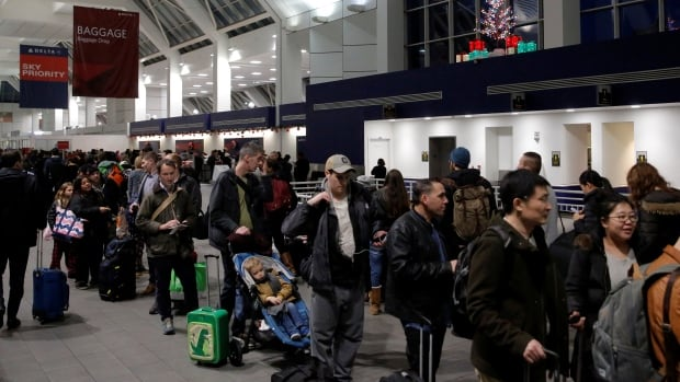 People line up for security ahead of the holidays at LaGuardia Airport in New York in December.  U.S. citizens are exempt from the new rule requiring non-visa travellers to get an electronic travel authorization before boarding a plane to Canada.