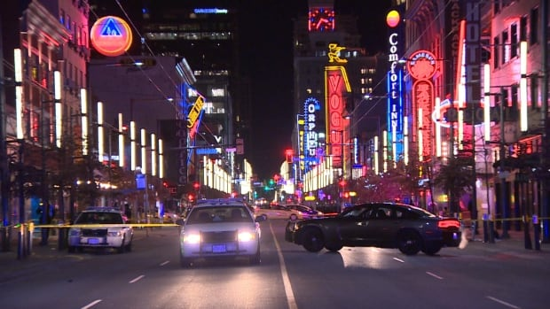 Police investigate a stabbing on Granville Street in January. The city has hit pause on a plan to close bars an hour early as part of a pilot project to address violence on the strip.