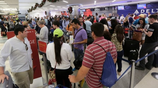 Passengers wait in line at the Delta airlines counter in Terminal 2 at the Fort Lauderdale-Hollywood International Airport on Saturday, the day after a gunman opened fire and killed five people.