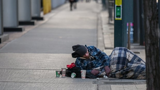 A man lies on the King Street sidewalk on Jan. 8 during an extreme cold alert. Toronto is mulling a name change for homeless shelters in hopes of lessening the stigma around them and signalling a new direction in housing homeless people.