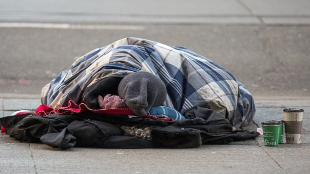 A homeless man lies sleeping on a downtown sidewalk during an extreme cold alert in Toronto. The city hopes a new tracking system will give them better data about homeless people who die outside of city-run shelters.