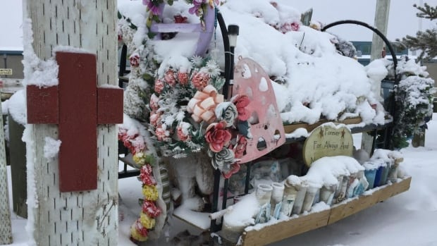Snow covers a memorial outside the La Loche Community School in Saskatchewan on Monday. Nearly a year ago, four people were killed in two shootings in the community.