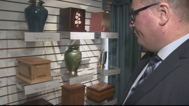 Kollin Weatherbee, owner of Sydney Memorial Chapel, looks at some of the urns available for sale at his funeral home.