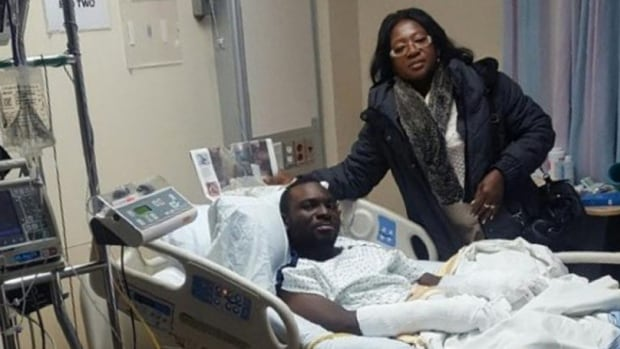 Maggie Yeboah, volunteer coordinator for African Communities of Manitoba and president of the Ghanaian Union of Manitoba, shown with Seidu Mohammed in hospital. Mohammed, a 24-year-old refugee from Ghana, was found on Highway 75 after crossing the US-Canada border and walking in the cold for several hours.
