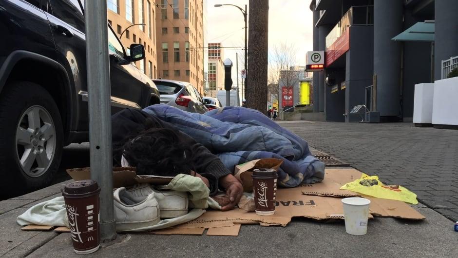 Man sleeping on cardboard near Robson street in Vancouver