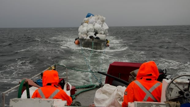 A crew with Ocean Legacy Foundation tows a barge of marine debris past Hesquiat Peninsula on the West Coast of Vancouver Island.