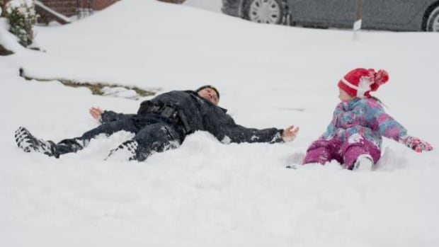 Time to make snow angels! Staff Sgt. Donna Mancuso didn't hesitate to get down into the snow while playing with some children Tuesday.