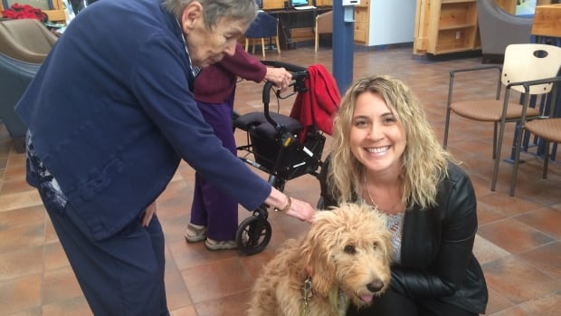 Angela Harvey holds Lily while Finlandia resident Mary pets the six-month-old goldendoodle. Harvey says the dog is well loved by the residents, staff and visitors.