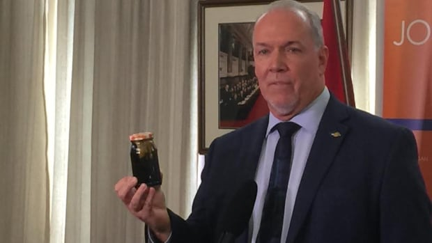 B.C. NDP Leader John Horgan holds up a jar of bitumen in January as he tells reporters the risks in approving the Trans Mountain pipeline expansion are too great.