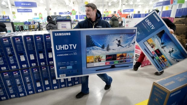 A customer carries a TV to the checkout at a Best Buy store in Ottawa on Boxing Day, Monday, Dec. 26, 2016. Between six and nine per cent of all goods sold each year by Canadian retailers will be returned, the bulk of them in the post-holiday period.