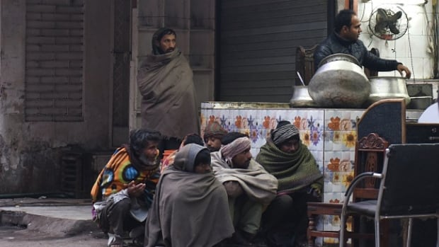 Homeless men wrapped in blankets wait for donors to purchase food for them from a stall on a cold morning in New Delhi. A cold wave is sweeping across South Asia, with many regions seeing the first snows of the winter season.