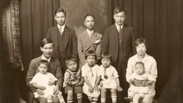 Yee Clun (bottom row far left, holding a child) fought the White Women's Labour Law in the 1920s. His story will be told as part of the Lost Stories Project.