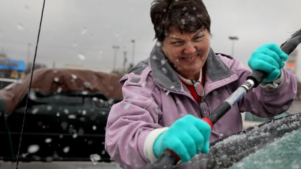 Mary Zinser scrapes a thick layer of ice off her windshield, Friday, Jan. 13, 2017, in Arnold, Mo. A thick glaze of ice covered roads from Oklahoma to southern Illinois on Friday amid a winter storm that caused numerous wrecks, forced school cancellations, grounded flights and prompted dire warnings for people to stay home.