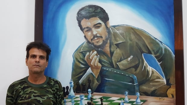 Cuban businessman Raudel Gutierrez Rodriguez stands by a photo of revolutionary leader Che Guevara at the chess club he manages in the northern city of Matanzas.