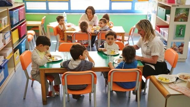 Children enjoy lunch in school room.