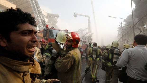 An Iranian firefighter cries after the iconic Plasco building collapsed after a fire in Tehran.