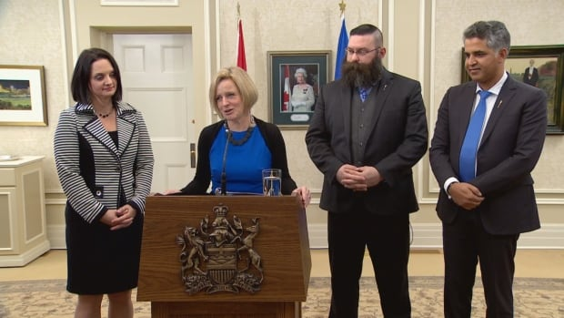 Premier Rachel Notley stands with new and reassigned ministers of her cabinet: Children's Services Minister Danielle Larivee, Municipal Affairs Minister Shaye Anderson, and Community and Social Services Minister Irfan Sabir.