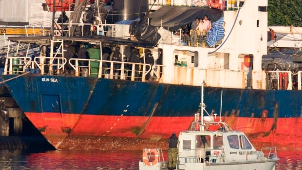 Migrants look over the side of the MV Sun Sea after it was escorted into CFB Esquimalt in Colwood, B.C., on Friday, Aug. 13, 2010.  The dilapidated cargo ship transported 492 Tamil migrants to Vancouver island.