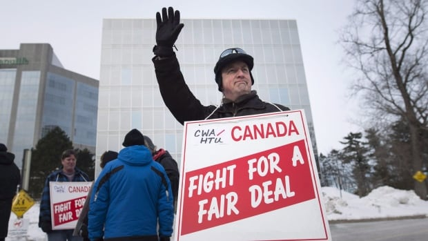 Eric Wynne waves to a supporter while joining other Halifax Chronicle Herald newsroom union members as they picket outside the newspaper's office after walking off the job in Halifax last year.