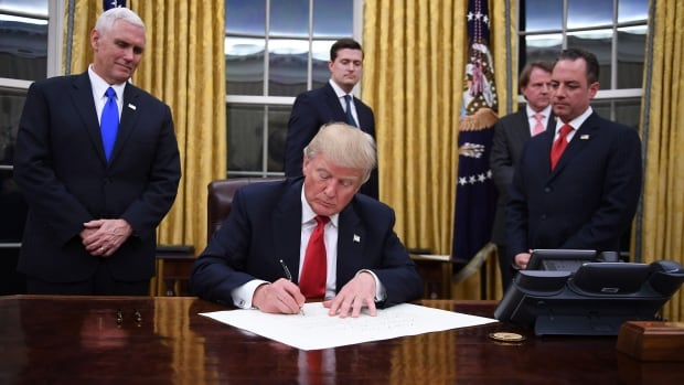 U.S. President Donald Trump signs an executive order as Vice-President Mike Pence and Chief of Staff Reince Priebus look on at the White House in Washington.