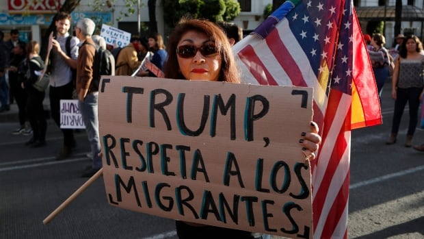 """A woman holds a sign that reads """"Trump, respect migrants"""" in Spanish during a march called by a local women's movement against U.S. President Donald Trump in Mexico City on Friday."""