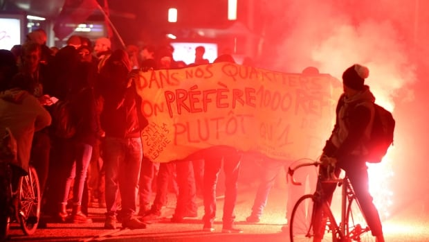 Protesters burn flares and hold a banner reading 'In our neighbourhoods we prefer 1,000 refugees to one of your fascists' in front of the town hall of Saint Martin d'Hères, near Grenoble, southeastern France, last year, during a counter-demonstration to a demonstration organized by the far-right Front National.