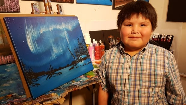 Joshua Wedzin, 9, paints alongside his artist father in his Behchoko, N.W.T., studio.