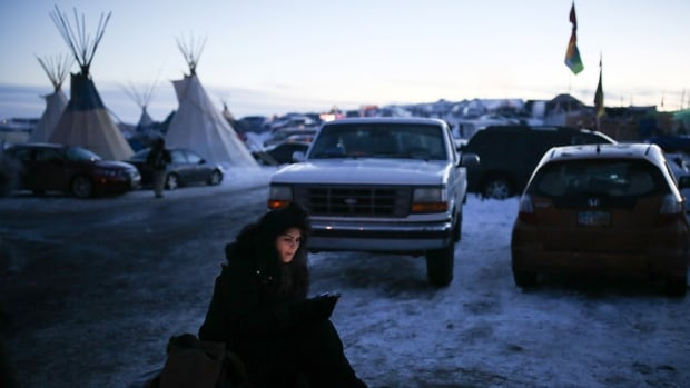A woman uses her smartphone in the Oceti Sakowin camp where 'water protectors' continue to demonstrate against plans to pass the Dakota Access pipeline.