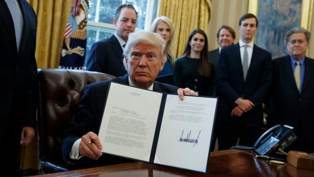 President Donald Trump shows his signature on a presidential memorandum on the Keystone XL pipeline, Tuesday, Jan. 24, 2017, in the Oval Office of the White House in Washington.