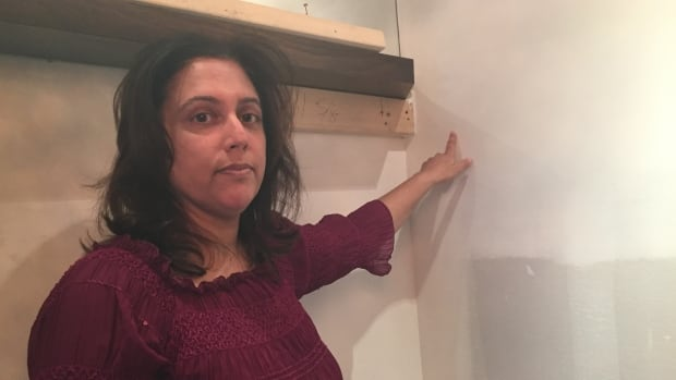 Jyoti Parmar points to the area where she found a hole in the drywall exposing a drain pipe. She believes a TV home renovation team mistakenly drilled holes in that pipe, causing it to leak.